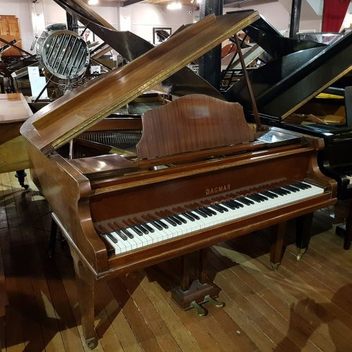 Used Dagmar baby grand piano finished in a mahogany case for sale.