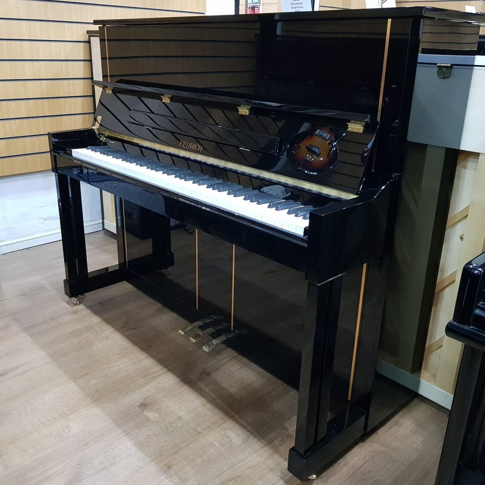 Feurich 125 Design upright piano, in a black polyester case, for sale.