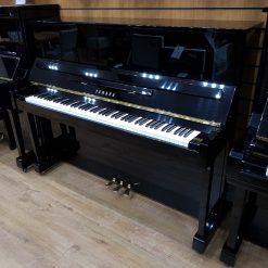 Used Yamaha E121T upright piano, in a black polyester case, for sale.