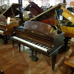 Used Challen baby grand piano for sale in a mahogany case.