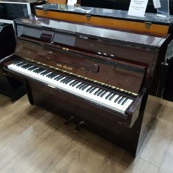 Used Karl Muller upright piano for sale, in a polyester mahogany case.